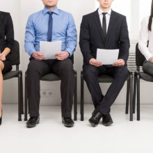 Recruitment: People seated waiting for interviews holding CVs