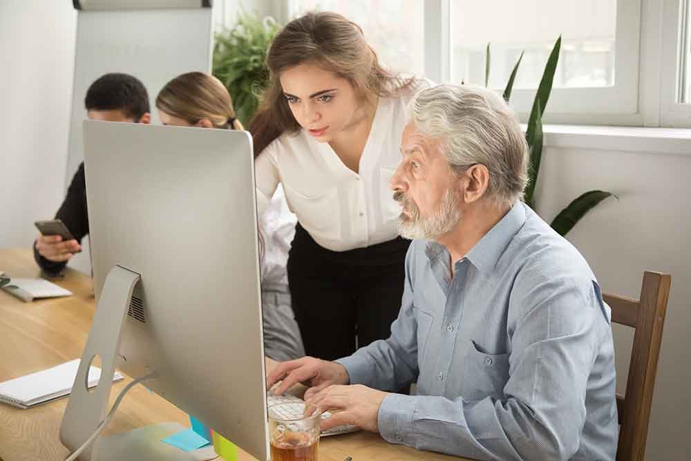 Older man and younger woman looking at a computer