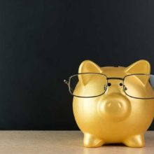 gold piggy bank wearing glasses