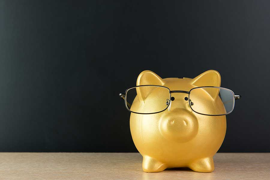 gold piggy bank wearing glasses indicating pensions