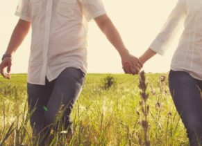 2 people holding hands in field of grass