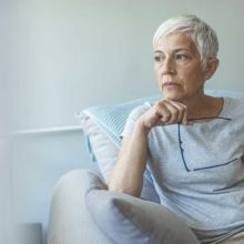 Older lady sits in armchair looking pensive