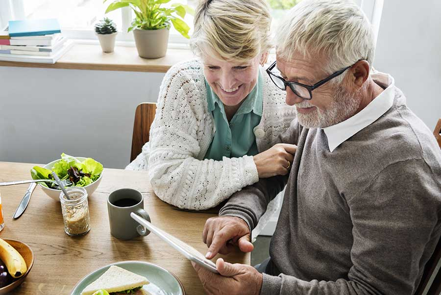 Older couple smile looking at a tablet over lunch