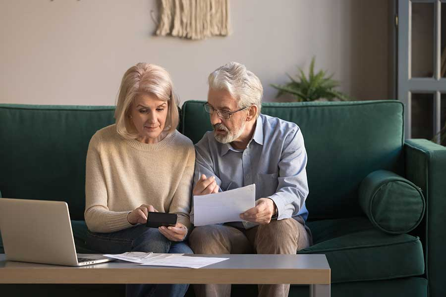 older couple sit on the sofa with a laptop and calculator