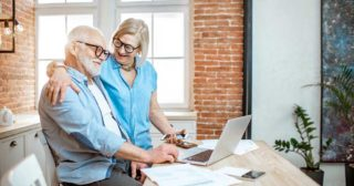Retirement age couple smiling and looking at a laptop