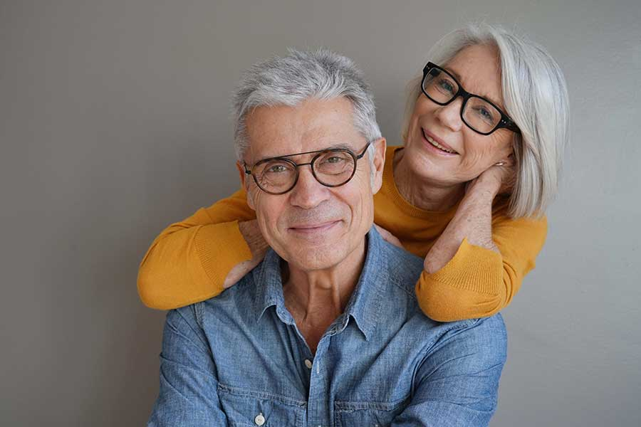 Older couple in bright clothing smile at the camera