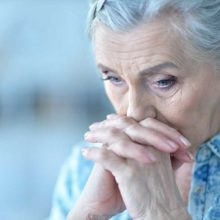 A worried pensioner with her hands to her face