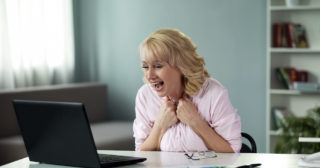 Woman over 50 reading an email about winning prize in online lottery, success