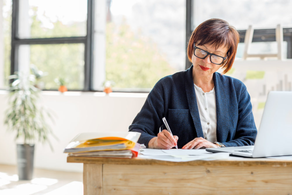 Senior business woman working part time on a laptop in bright modern office interior