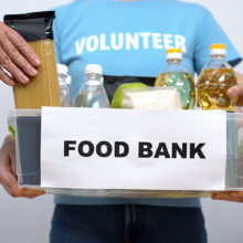 volunteer holds box with food bank items inside