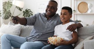 Grandparent and grandson watch tv with popcorn