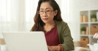 Older woman works at home on laptop