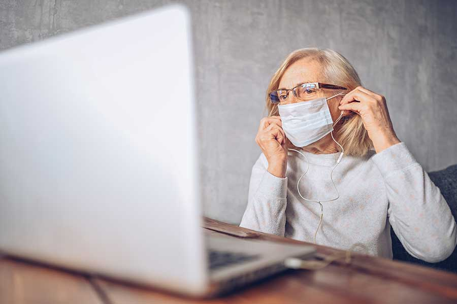 Older woman works at laptop with facemask on