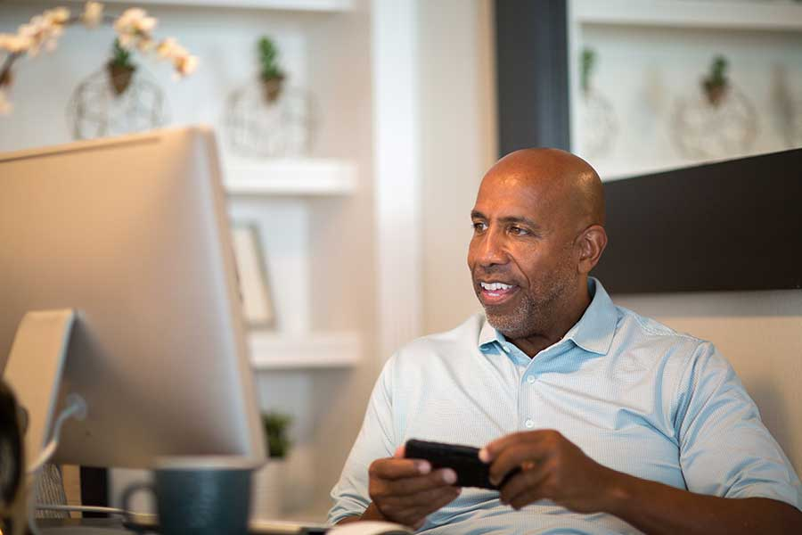 Older man looks at mobile phone and computer working at home