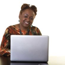 Smiling woman works at laptop