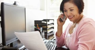 Smiling woman at work desk on phone