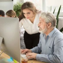 Older man being instructed while doing work on a monitor in an office