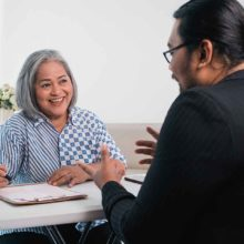 Woman smiling interviewing a man sitting opposite her