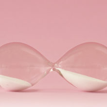 Hourglass lying on pink background - Concept of menopause