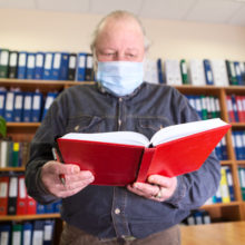 Senior male archivist holding open red notebook in hands, looking at camera, man wearing face mask due Covid-19 pandemic